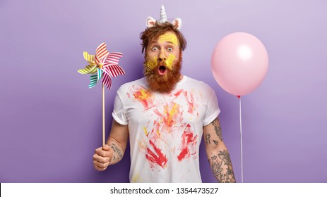 Indoor shot of surprised red man stares with shock, holds balloon and windmill in both hands, wears unicorn headband with horn and ears, smearked with colorful paints, entertains children on party