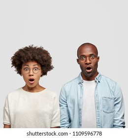 Indoor shot of terrified African American couple recieve bill, have no money to pay, stare at camera with surprised stunned expressions. Attractive dark skinned female has Afro hairstyle with friend