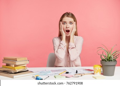 Indoor shot of terrified female keeps hand on head, opens mouth widely, forgets to do one more task, being tired and exhausted as prepares for session, reads books and writes notes, want get good mark