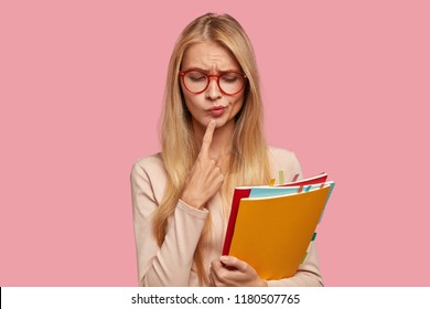 Indoor shot of thoughtful puzzled attractive scientist holds fore finger on chin, looks with puzzlement down, thinks on creation new book, dressed in casual beige sweater, isolated on pink wall