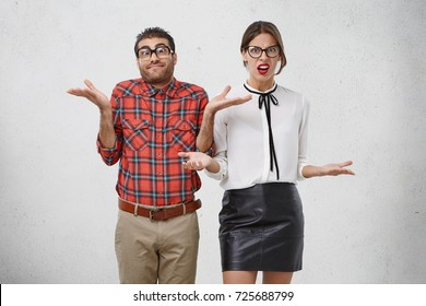 Indoor shot of uncertain man and woman in formal clothes shrug shoulders, don`t know answer or way out, look displeased and dissatisfied. Two smart students don`t understand difficult material
