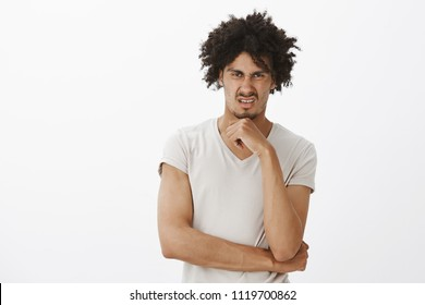 Indoor shot of unimpressed attractive gay model with tanned skin and afro haircut, wrinkling nose and gazing with dislike and antipathy, holding palm above chin, frowning, being unimpressed