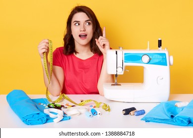 Indoor shot of woman seamstress sitting at table with sewing machine with opened mouth, has new great idea for new dress. Sewer wears red casual t shirt posing isolated over yellow background.