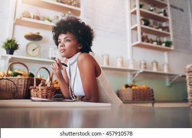 Indoor shot of young african female juice bar owner looking away and thinking, she is standing behind bar counter.