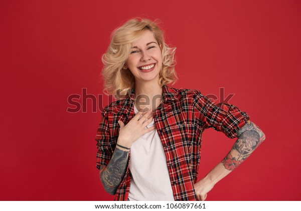 Indoor shot of young blonde female smiling and keep her hand at waist. Wears red checkered shirt. Tattoo over her arms. Isolated over red background