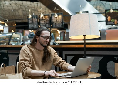 Indoor shot of young photographer working on laptop, retouching pictures sitting at round table in shopping center interior. Male student in eyewear doing home assignment on notebook computer