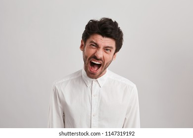 Indoor shot of young unshaven businessman screams and feel mad and angry, because the project isn't done. Negative facial expression. Isolated over white wall