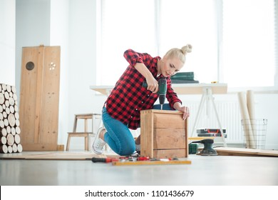 Indoor shot of young woman repairing furniture at home, sitting on the floor.