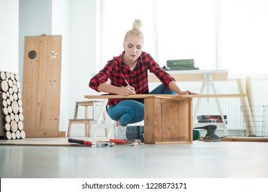 Indoor shot of young woman repairing furniture at home.