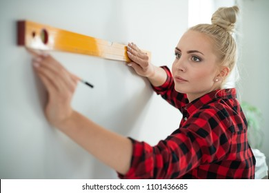Indoor shot of young woman using leveling tool at home. Close up of face.