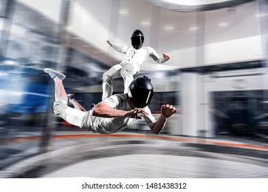 Indoor skydive tunnel. Surf sky . Men surfing on back of his friend. Indoor skydiving skysurfing. Free fall in wind tunnel.