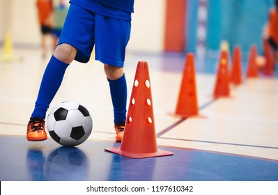 Indoor soccer players training with balls. Indoor soccer sports hall. Indoor football futsal player, ball, futsal floor and red cone. Futsal training dribbling drill. Sports background. Futsal league.