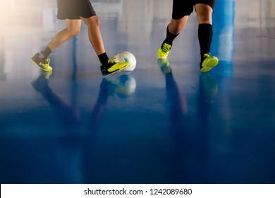 Indoor soccer sports hall. Football futsal player, ball, futsal floor. Sports background. Youth futsal league. Indoor football players with classic soccer ball.