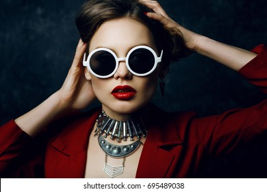 Indoor studio close up portrait of young beautiful woman wearing stylish round white sunglasses, big silver boho necklace, red jacket. Model with red lips, long hair. Female beauty, fashion concept