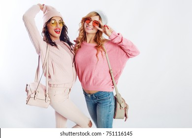 Indoor studio image of two girls, happy friends in stylish pink clothes and hat spelling funny  the together. White background. Trendy hat and glasses.Showing peace.