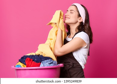 Indoor studio shot of charming smiling black haired housewife with closed eyes, standing after laundry with pink basin near her, feeling smell of fresh clean clothes, holding shirt. House chores.
