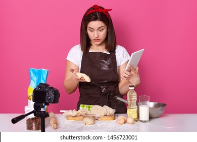Indoor studio shot of surprised housewife having shocked facial expression, looking at dough with wide opened eyes, holding tablet in hand, trying new recipe, recording culinary video. Cook concept.