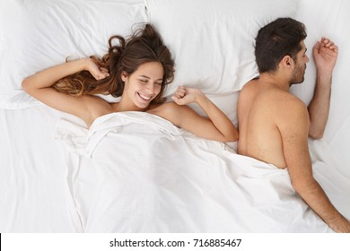 Indoor top view of happy positive smiling woman waking up early in the morning, lying in bed with her sleeping bearded husband, stretching slowly, having joyful look, full of energy, ready for new day