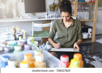Indoor view of beautiful young Caucasian woman artist with brunette hair busy making drawings in spacious workshop interior with lots of paint bottles on table and computer monitor in background