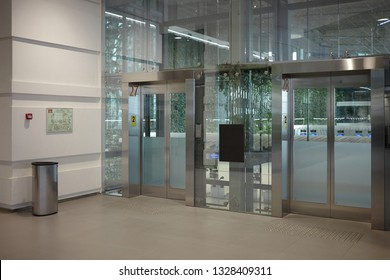 Indoor view of empty clean entrance in international airport terminal with stylish modern automatic transparent glass doors. Urban lifestyle, interior, construction, architecture and design concept