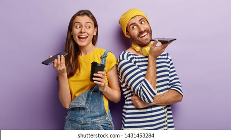 Indoor view of happy woman and man keep modern cell phones near mouthes, make voice call, enjoy nice conversation, drink hot beverage from disposable cup, stand back to each other over purple wall
