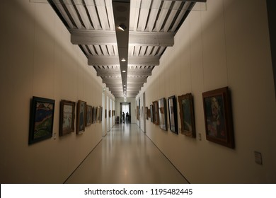 Indoor view of a long exhibition corridor at Fabre museum in Montpellier city, France. September, 15, 2018. Leading lines with light from the ceiling. Paintings aligned on the clear white walls.