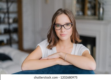 Indoor view of pretty woman in spectacles, keeps hands on back of sofa, poses in living room at home, thinks about something, dressed in casual clothes. People, free time and lifestyle concept