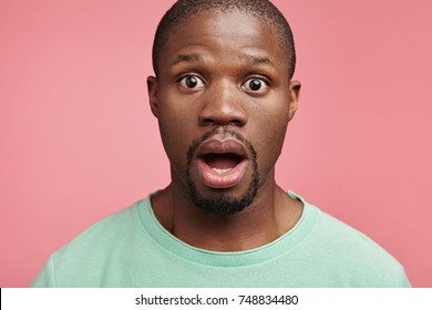 Indoor view of surprised man watches film with opened mouth, sees shocking scene, amazed by unexpected finish. Male office worker being told off by strict employee for coming late on meeting