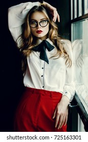 Indoor waist up portrait of young beautiful fashionable business woman posing on dark background. Lady wearing stylish eyeglasses, golden wrist watch. Female fashion concept.