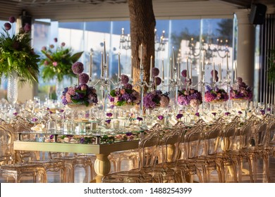 indoor wedding table with flowers candles and chandeliers