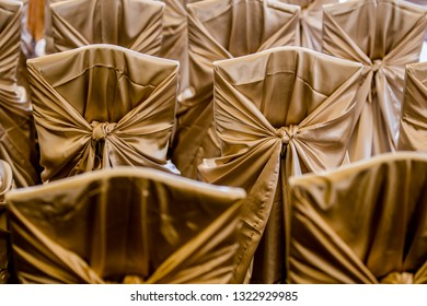 Indoor wedding. White cloth cover with a cloth and tied with a bow decorations