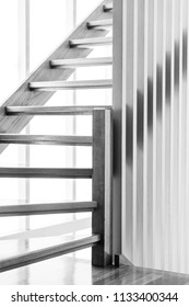 Indoor wooden staircase with light behind it in black and white