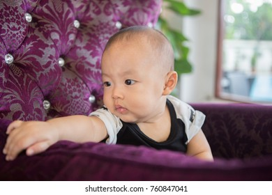 Indoor zooming closeup portrait of a young lovely charming young handsome Asian boy baby dresses in black and white sitting on a large decorative purple couch with blurry background of window frame