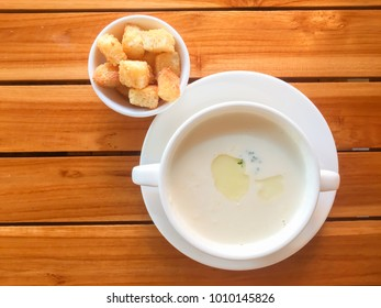 Indoor zooming closeup top view of delicious chicken cream soup serves with piece of garlic bread on rounded ceramic whitish dishes on brownish wooden table inside a modern local rural restaurant