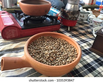 Indoor zooming closeup view teeming civet coffee seeds contain in vintage rounded earthenware bowl preparing to cooked in front of another pot and ingredients