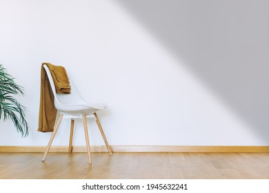 Indoors flat wall mockup with green potted houseplant and chair with clothes in minimalist style. Interior in airy light scandinavian style with wooden floor