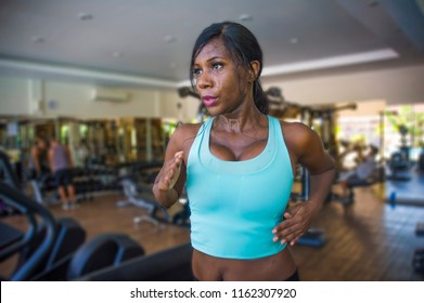 indoors gym portrait of young attractive black afro American woman training hard all sweaty at fitness club a treadmill running workout in body care and runner healthy lifestyle concept
