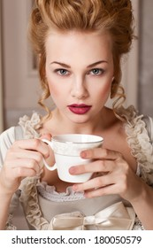 Indoors shot in the Marie Antoinette style, drinking tea