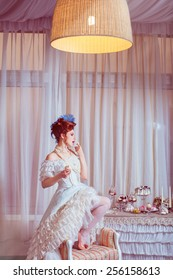 Indoors shot in the Marie Antoinette style. Woman licking a finger with cream.