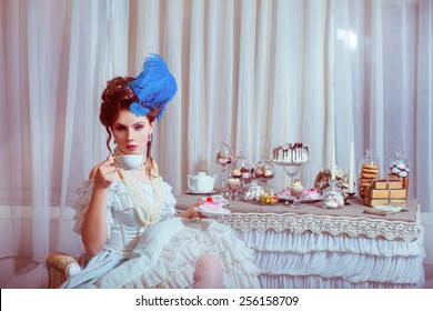 Indoors shot in the Marie Antoinette style. Woman drinking tea with sweets.
