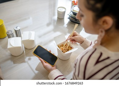 Indoors. Woman hands holding phone and chopsticks in the kitchen