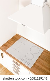 Induction cooktop in modern kitchen with hood from above.