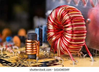 Inductor copper wire winding. Electronic components soldered in circuit board. Toroidal and cylindrical induction coils. Dismantled computer power supply unit detail. Reflection on aluminium heatsink.