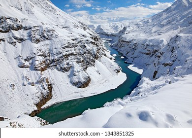 Indus river in Hemis NP, Ladak, India. River with snow during winter, Himalayas. Mountain landscape in India wild nature. Sunny day with snow in the valley, blue sky with white clouds.
