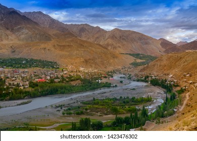 Indus river turns around Kargil City valley with Himalayan mountains and blue cloudy sky in background, Leh, Ladakh, Jammu and Kashmir, India
