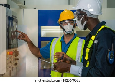 industrail background of factory workers wearing face mask to protect coronavirus covid-19 with safety vest and helmet having working detail brief from factory foreman in control room