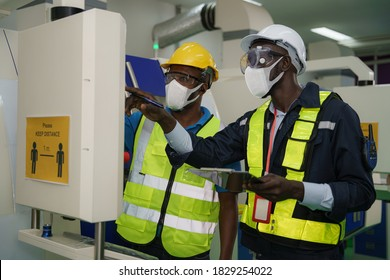 industrail background of factory workers wearing face mask to protect coronavirus covid-19 with safety vest and helmet having working inspection from factory foreman in control room
