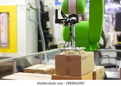 Industrail Robotic Arm holding package in an industry packaging line. Industrial 4.0 technology for modern factory management. Robotic arm use with vacuum system for packaging line in a factory.