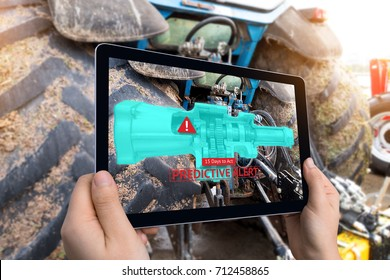 Industrial 4.0 , Augmented reality technology , smart agriculture and farm concept. Hand holding tablet with AR maintenance application and predictive alert for check destroy part of smart machine.