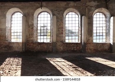 Industrial abandoned, devastated interior of old building with bright light coming through windows, architectural remains